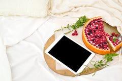 Desayuno plano de la endecha en cama con el pastel de queso de la frambuesa, el té y el cuaderno abierto, tableta de la menta Fotografía de archivo libre de regalías