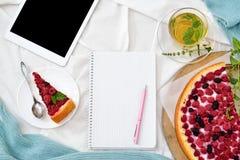 Desayuno plano de la endecha en cama con el pastel de queso de la frambuesa, el té y el cuaderno abierto, tableta de la menta Imagen de archivo