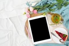 Desayuno plano de la endecha en cama con el pastel de queso de la frambuesa, el té y el cuaderno abierto, tableta de la menta Imagen de archivo libre de regalías