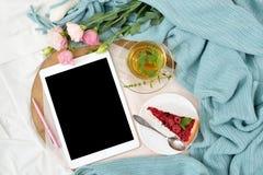 Desayuno plano de la endecha en cama con el pastel de queso de la frambuesa, el té y el cuaderno abierto, tableta de la menta Fotografía de archivo