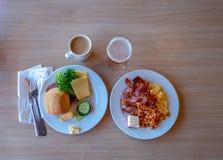 Desayuno que consiste en dos placas y cafés con leche y un poco de zumo de manzana imagen de archivo libre de regalías