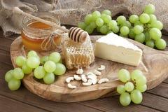 Desayuno: queso con la uva, las nueces y la miel Foto de archivo libre de regalías