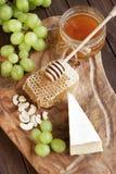 Desayuno: queso con la uva, las nueces y la miel Fotografía de archivo libre de regalías
