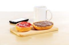 Desayuno rápido con la taza de rollo de pan de café y de teléfono móvil Foto de archivo