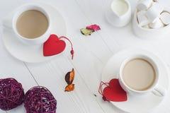 Desayuno romántico con las tazas blancas de los pares de café en blanco Imagen de archivo