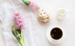 Desayuno romántico de la mañana, taza de café, jarro de leche y torta con la decoración del jacinto rosado Concepto del resorte Foto de archivo