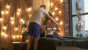 Desayuno romántico de la porción del hombre a la mujer en cama almacen de video