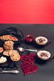 Desayuno romántico dos tazas de café, de capuchino con las galletas del chocolate y de galletas cerca de corazones rojos en fondo Fotos de archivo libres de regalías