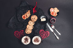 Desayuno romántico dos tazas de café, de capuchino con las galletas del chocolate y de galletas cerca de corazones rojos en fondo Fotografía de archivo