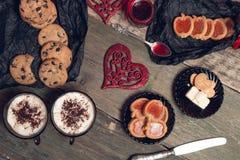 Desayuno romántico dos tazas de café, de capuchino con las galletas del chocolate y de galletas cerca de corazones rojos en fondo Imagen de archivo