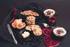 Desayuno romántico dos tazas de café, de capuchino con las galletas del chocolate y de galletas cerca de corazones rojos en fondo Foto de archivo libre de regalías