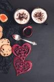 Desayuno romántico dos tazas de café, de capuchino con las galletas del chocolate y de galletas cerca de corazones rojos en fondo Fotos de archivo