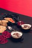 Desayuno romántico dos tazas de café, de capuchino con las galletas del chocolate y de galletas cerca de corazones rojos en fondo Foto de archivo