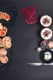 Desayuno romántico dos tazas de café, de capuchino con las galletas del chocolate y de galletas cerca de corazones rojos en fondo Imagen de archivo libre de regalías