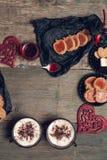 Desayuno romántico dos tazas de café, de capuchino con las galletas del chocolate y de galletas cerca de corazones rojos en fondo Fotografía de archivo libre de regalías