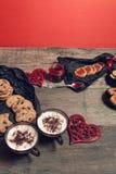 Desayuno romántico dos tazas de café, de capuchino con las galletas del chocolate y de galletas cerca de corazones rojos en fondo Imágenes de archivo libres de regalías