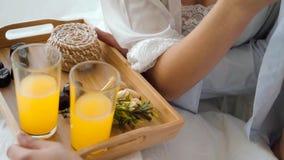 Desayuno romántico en lecho en casa Bandeja de madera con el jugo y los dulces en la cama almacen de metraje de vídeo
