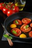 Desayuno sabroso: huevos fritos con los tomates, cocinando Fotografía de archivo