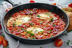 Desayuno sabroso Shakshuka en una cacerola del hierro Huevos fritos con los tomates, rojo, pimientas amarillas, cebolla, perejil, Imágenes de archivo libres de regalías