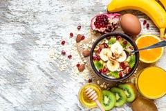 Desayuno sano con el cuenco de harina de avena de la fruta, de huevo y de zumo de naranja Fotos de archivo
