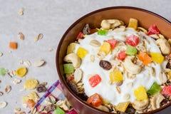 Desayuno sano con el yogur, el muesli y la fruta escarchada en cuenco de cerámica en el fondo de piedra Fotografía de archivo libre de regalías
