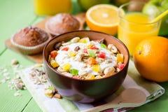 Desayuno sano con el yogur, el muesli y la fruta escarchada en cuenco de cerámica en fondo de madera verde Fotos de archivo libres de regalías