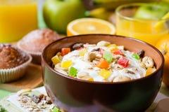 Desayuno sano con el yogur, el muesli y la fruta escarchada en cuenco de cerámica en fondo de madera verde fotografía de archivo