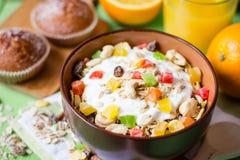 Desayuno sano con el yogur, el muesli y la fruta escarchada en cuenco de cerámica en fondo de madera verde imagen de archivo