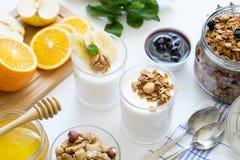 Desayuno sano con el yogur en vidrio, granola y frutas Imagenes de archivo