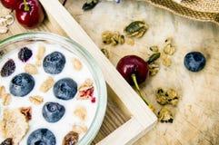 Desayuno sano con el yogur, el granola y el muesli frescos con la cereza y las bayas en peque?o vidrio en la bandeja de madera, c fotografía de archivo libre de regalías