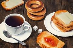 Desayuno sano con la taza de té, de pan, de mantequilla y de atasco Imágenes de archivo libres de regalías