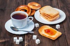 Desayuno sano con la taza de té, de pan, de mantequilla y de atasco Fotos de archivo