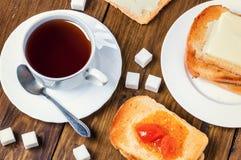 Desayuno sano con la taza de té, de pan, de mantequilla y de atasco Imagenes de archivo