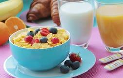 Desayuno sano con las avenas, la leche, los cruasanes, el zumo de naranja y las frutas frescas como plátano, naranjas, las fresas Fotografía de archivo libre de regalías
