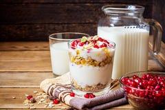 Desayuno sano con las semillas del yogur, del muesli y de la granada en vidrio en fondo de madera imagen de archivo libre de regalías