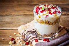 Desayuno sano con las semillas del yogur, del muesli y de la granada en vidrio en fondo de madera imágenes de archivo libres de regalías