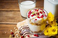 Desayuno sano con las semillas del yogur, del muesli y de la granada en vidrio en fondo de madera fotografía de archivo libre de regalías