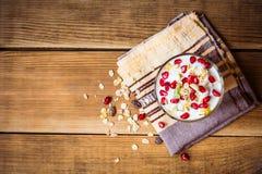 Desayuno sano con las semillas del yogur, del muesli y de la granada en vidrio en fondo de madera Foto de archivo