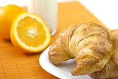 Desayuno sano con los croissants, la naranja y la leche Foto de archivo libre de regalías