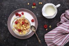 Desayuno sano con los fruts integrales de las escamas y leche en TA oscura Foto de archivo