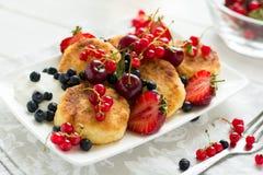 Desayuno sano: crepes del queso con crema agria y bayas maduras frescas Imagenes de archivo