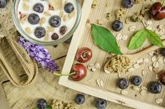 Desayuno sano de la visión superior con el yogur, el granola y el muesli frescos con la cereza y las bayas en pequeño vidrio en l imagenes de archivo