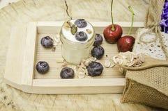 Desayuno sano de la visión superior con el yogur, el granola y el muesli frescos con la cereza y las bayas en pequeño vidrio en l foto de archivo
