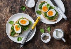 Desayuno sano delicioso - bocadillo asado a la parrilla del pan con espinaca y huevos hervidos en fondo de madera Foto de archivo libre de regalías