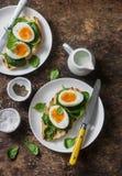 Desayuno sano delicioso - bocadillo asado a la parrilla del pan con espinaca y huevos hervidos en fondo de madera Fotos de archivo