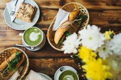 Desayuno sano en el restaurante: las tazas de té con leche verde llamaron Matcha, el postre y los bocadillos con las verduras Fotografía de archivo libre de regalías