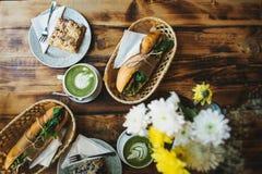 Desayuno sano en el restaurante: las tazas de té con leche verde llamaron Matcha, el postre y los bocadillos con las verduras Imagen de archivo