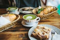 Desayuno sano en el restaurante: las tazas de té con leche verde llamaron Matcha, el postre y los bocadillos con las verduras Imagenes de archivo