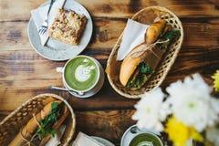 Desayuno sano en el restaurante: las tazas de té con leche verde llamaron Matcha, el postre y los bocadillos con las verduras Fotos de archivo