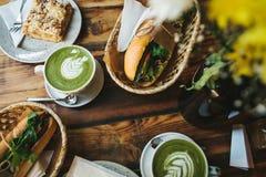 Desayuno sano en el restaurante: las tazas de té con leche verde llamaron Matcha, el postre y los bocadillos con las verduras Imagen de archivo libre de regalías